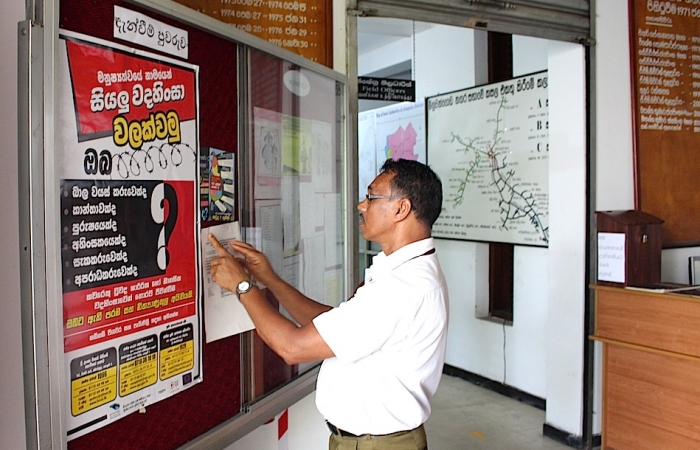 A man reads NPC's anti-torture poster in Gampaha
